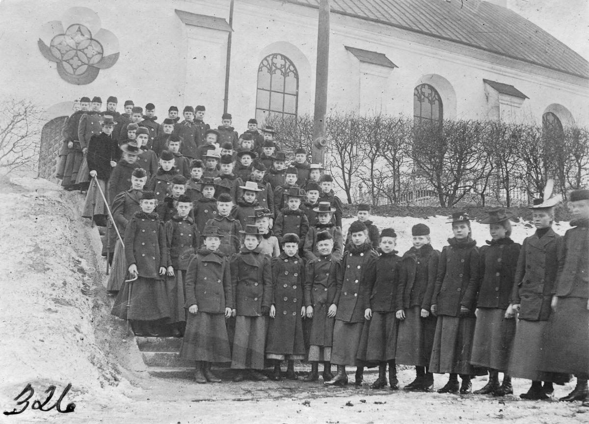 Unga uniformerade flickor utanför Köpings kyrka. Omkring 1900.