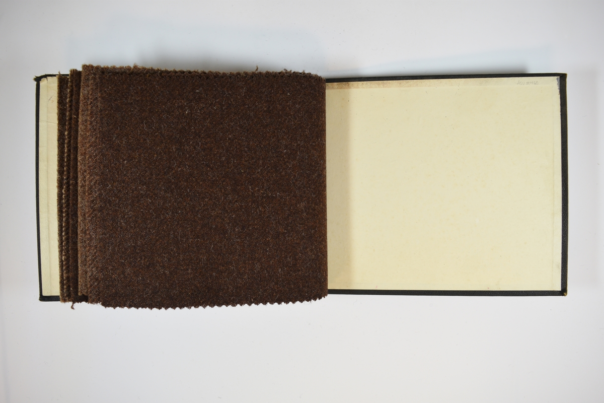 Prøvebok med 6 stoffprøver. Middels tykke stoff, tre stykker med rutemønster, tre ensfargede. Stoffene ligger brettet dobbelt i boken. Stoffene er merket med en rund papirlapp, festet til stoffet med metallstifter, hvor nummer er påført for hånd. Innskriften på innsiden av forsideomslaget indikerer at alle stoffene har kvaliteten 167B.   Stoff nr.: 167B/25, 167B/26, 167B/27, 167B/28, 167B/29, 167B/30.