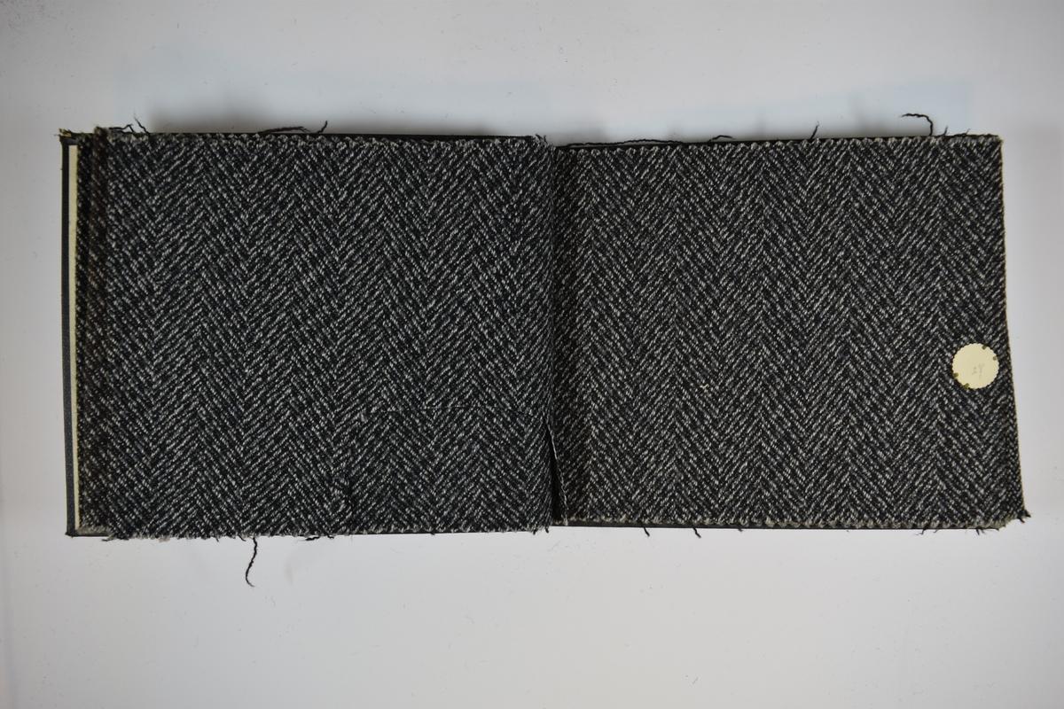 Prøvebok med 6 stoffprøver. Middels tykke stoff med fiskebensmønster. Stoffene ligger brettet dobbelt i boken slik at vranga dekkes. Stoffene er merket med en rund papirlapp, festet til stoffet med metallstifter, hvor nummer er påført for hånd. Innskriften på innsiden av forsideomslaget indikerer at alle stoffene har kvaliteten 175.   Stoff nr.: 172/25, 175/26, 175/27, 175/28, 175/29, 175/30.