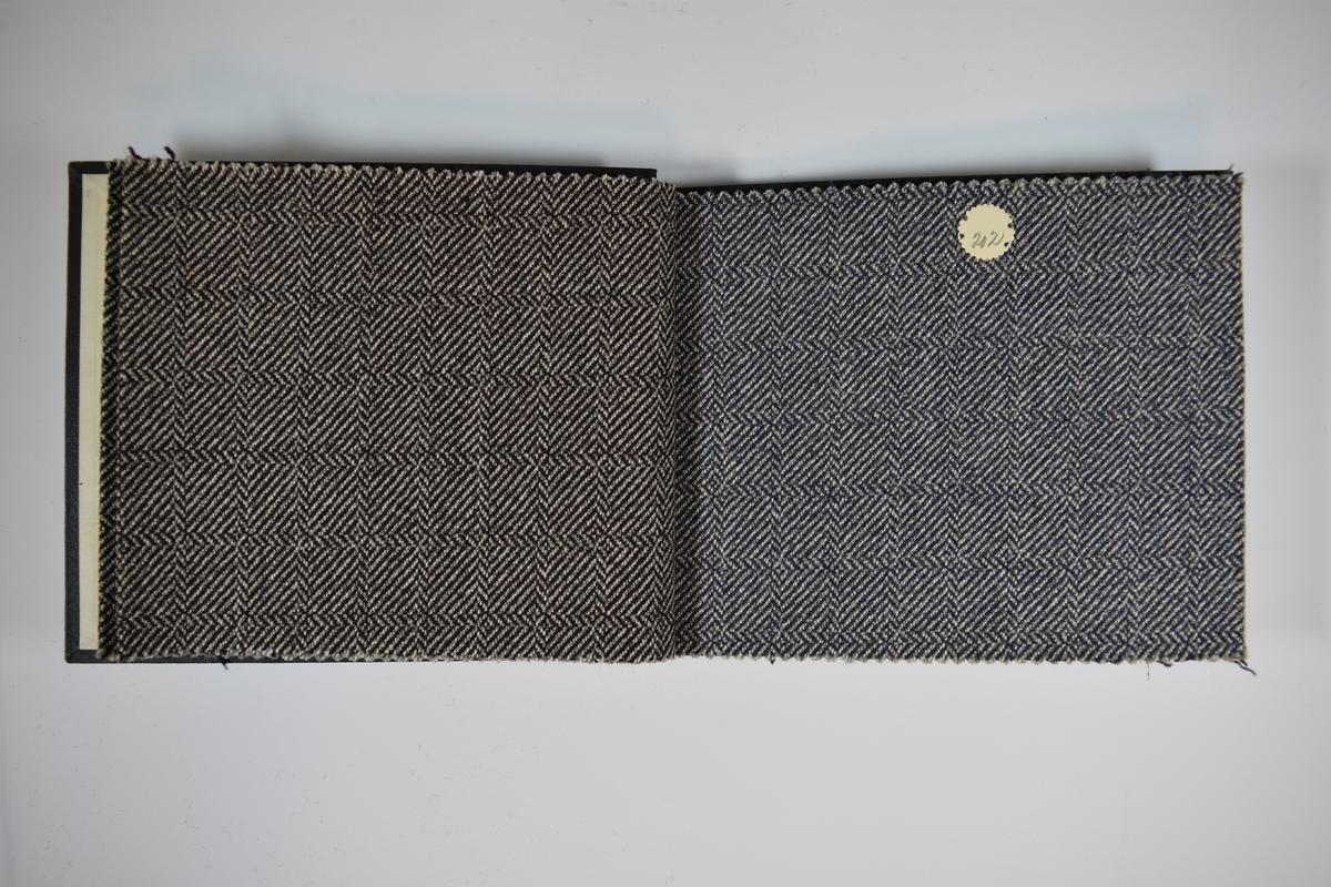 Prøvebok med 5 stoffprøver. Middels tykke stoff med fiskebensmønster eller lignende. Stoffene ligger brettet dobbelt slik at vranga skjules. Stoffene er merket med en rund papirlapp, festet til stoffet med metallstifter, hvor nummer er påført for hånd. Innskriften på innsiden av forsideomslaget indikerer at alle stoffene har kvaliteten 175B.   Stoff nr.: 175B/200, 175B/201, 175B/202, 175B/203, 175B/204.
