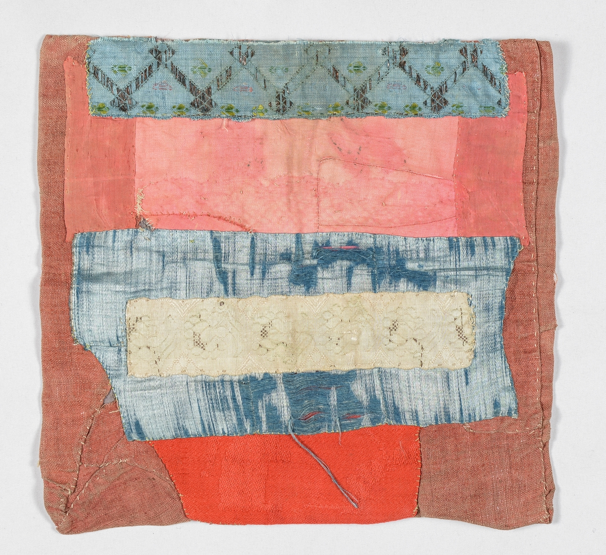 Bringeduk rosa og blå silke.  Blått ripsband med mettallmønster i kanten oppe, under bandet er det også kanta med blå silke. Bakstykket er i raudt lintøy.