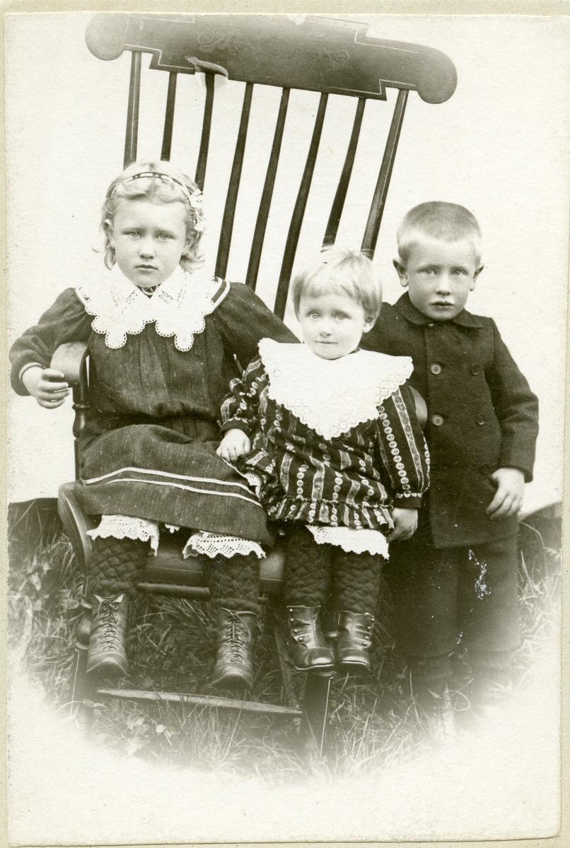 To jenter og ein gut sit i ein gyngestol. Truleg tatt 1910.