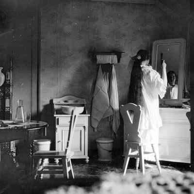 Kvinne grer segpå soveværelse, 1905 (Foto/Photo)