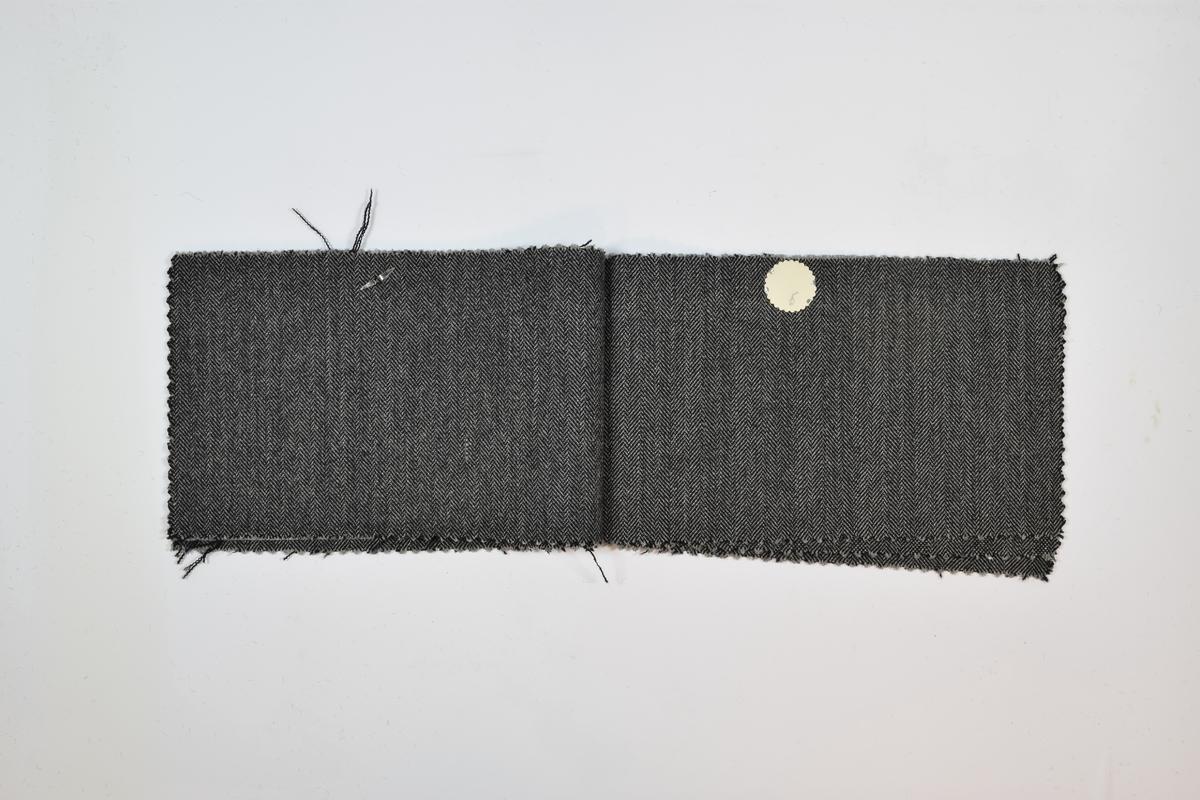 Sammenstiftede stoffprøver, 7 ulike stoff. Relativt tynne stoff med fiskebensmønster blant annet. Mønsteret på de tre første stoffene er likt, men fargen varierer. På de resterende stoffene er mønsteret ulikt, men fargen den samme. Stoffprøvene er klippet med sikksakk-saks langs alle kanter. Alle stoffer er merket med en rund papirlapp festet med metallstifter hvor nummer er påskrevet for hånd. Det er rimelig å anta at alle stoffene har kvalitetsnummer 1766 grunnet plasseringen av tallene på lappene, samt likheten mellom stoffene.   Stoff nr. 1766/1, 1766/2, 1766/3, 1766/4, 1766/5, 1766/6, 1766/7.