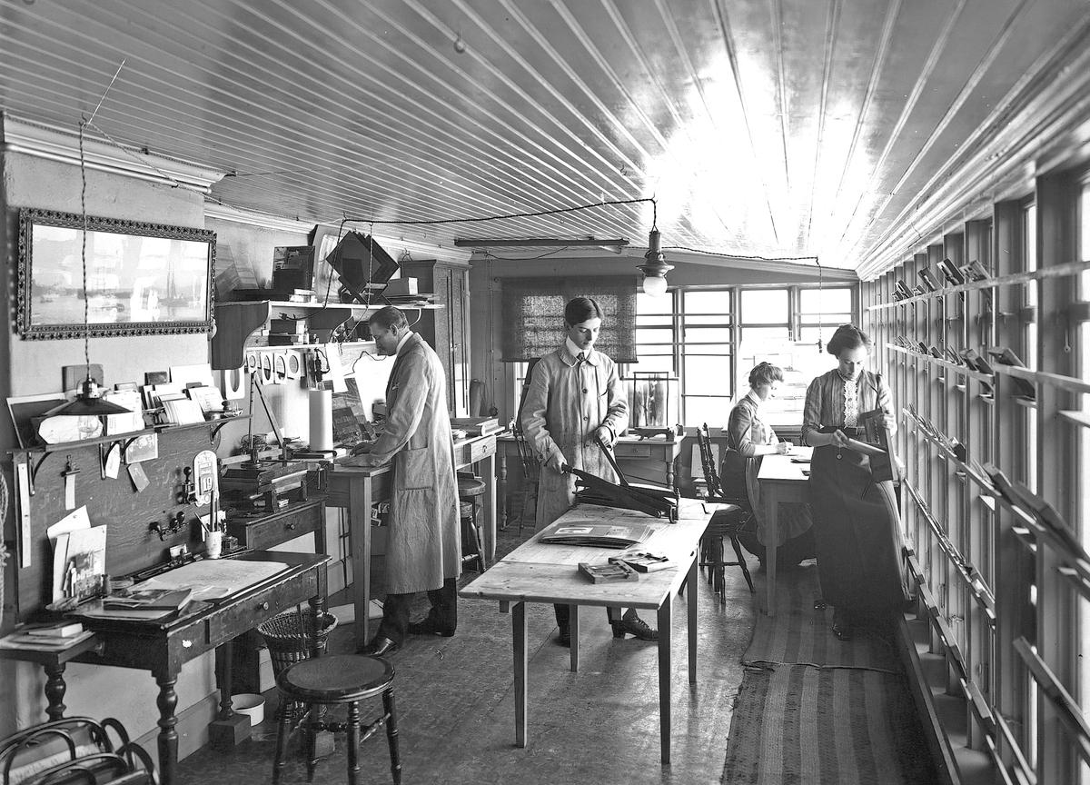 Reimers fotografiska ateljé, arbetsrummet. Onsdagen den 19 mars 1913. Till vänster fotograf Gustaf Reimers, i mitten Gunnar Hermansson.