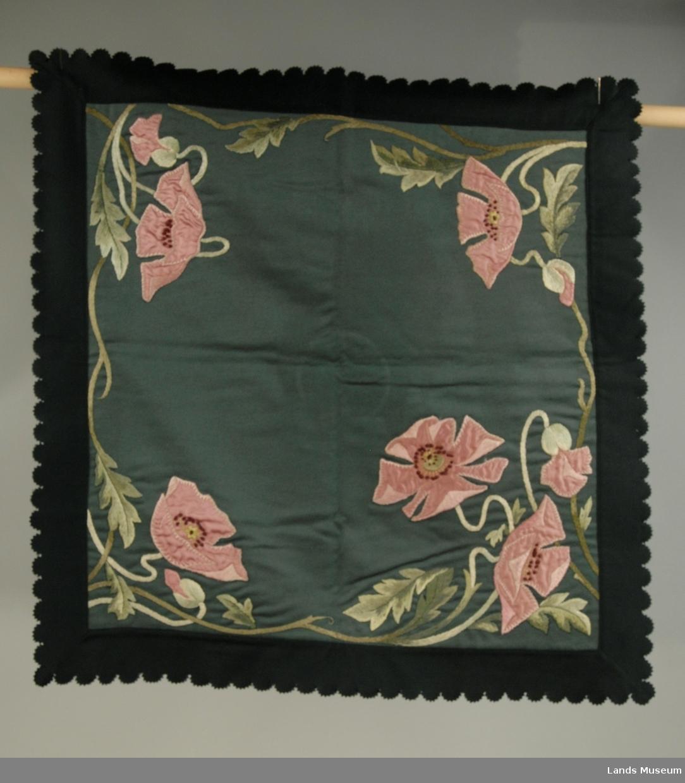 Applikerte valmuer i rosa silke og broderte blad i fleire sjatteringer av grønt. Påsatt kant i mørkegrønn filt rundt. Foret på baksiden.