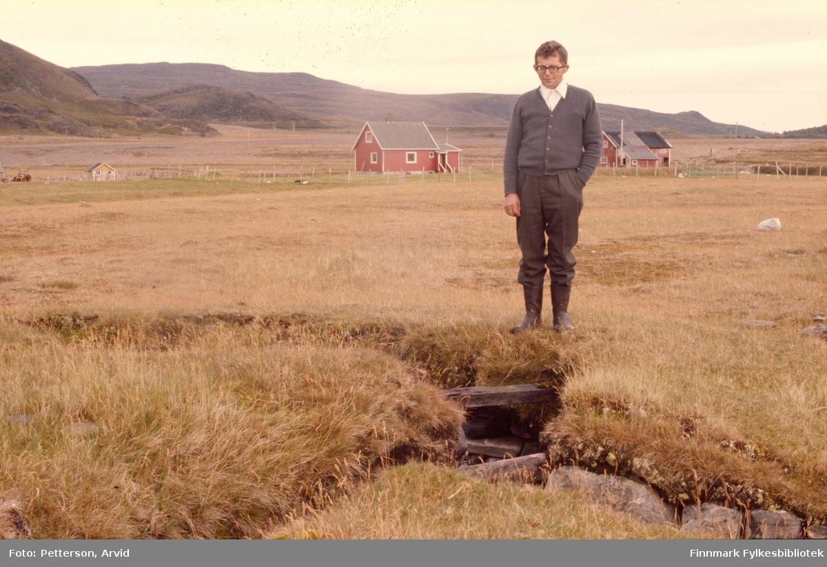 Paul Andersen ved festningsanlegg, i bakgrunn Andersens jordbruk i Selkopp i Kokelv. Bildet er tatt på 1970-tallet.