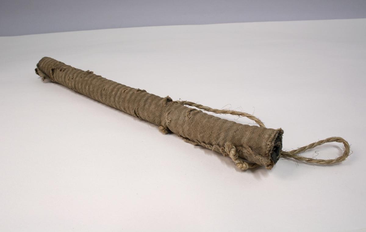 Hjemmelaget kølle laget av en avstivet slange. På to steder er køllen gjennomhullet, og i hullene er det festet tau. Køllen er trukket med strie som har revnet noe enkelte steder.