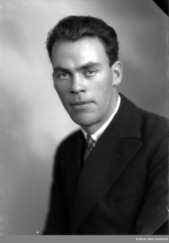 Ateljébild på en okänd man i kostym och slips. Beställare till bilden: Herr Helge Lindman ifrån Kalmar.