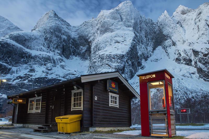 Rød telefonkiosk ved fjell og hus fra vegvesenet (Foto/Photo)