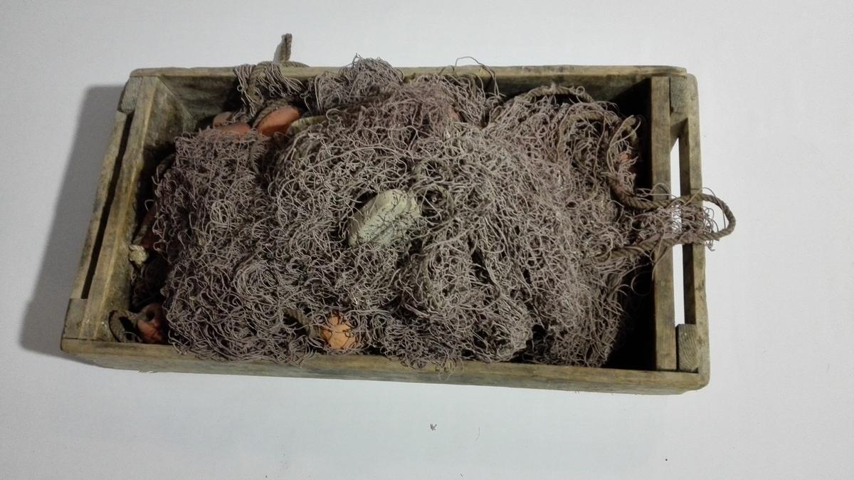 """Lys brun trollgarn av bomull, med naturkork som flytemedium og rustraud gjennomhola syliinderforma teglstein som søkke. Småmaska garn, (3,5 cm frå knute til knute) med stormaska garn (""""trollmaskar"""") på kvar side (20 cm frå knute til knute).  Garnet ligg i trekasse DHS.32558"""