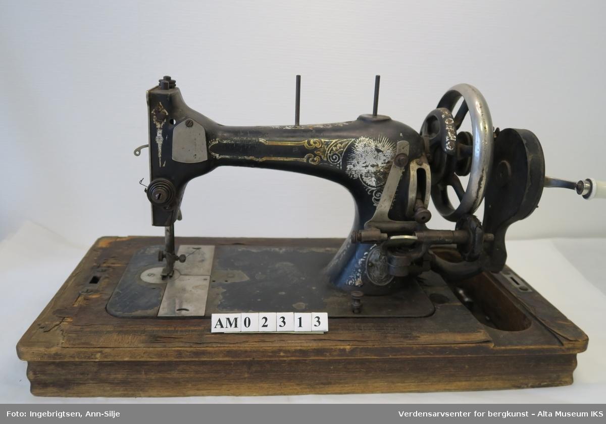 Symaskin av gammel type. Et lite hjul til å mate undertråden. Står på en finert tresokkel som er dekorert med intarsia. Selve maskinen er dekorert med border. Tilpasset remdrift. På maskinen er det en medaljong med en logo av en S og en løve eller lignende.