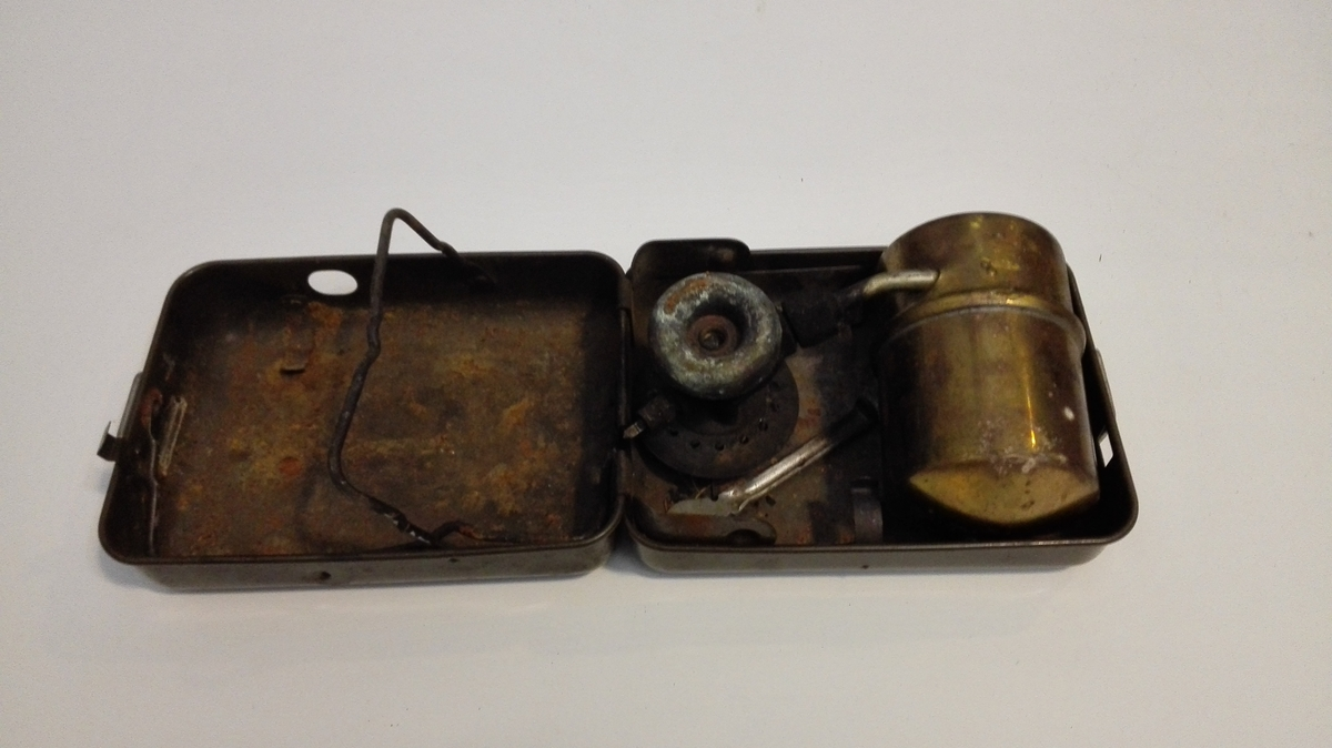 Kokeapparat i sammenleggbar metallboks iLten tank for parafin, med pumpe, og røyr til separat brennar. Ein fastnøkkel ligg i boksen.