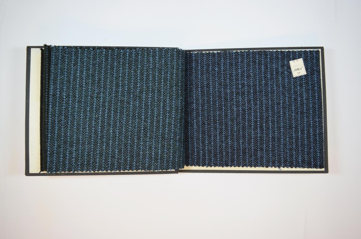 Rektangulær prøvebok med fire stoffprøver og harde permer. Permene er laget av hard kartong og er trukket med sort tynn tekstil. Boken inneholder middels tykke stoff med striper. Toskaftsvev? Stoffene ligger brettet dobbelt i boken slik at vranga skjules. Stoffene er merket med en firkantet papirlapp, festet til stoffet med metallstifter, hvor nummer er påført for hånd.   Stoff nr.: 2065/8, 2065/9, 2065/10, 2065/11.