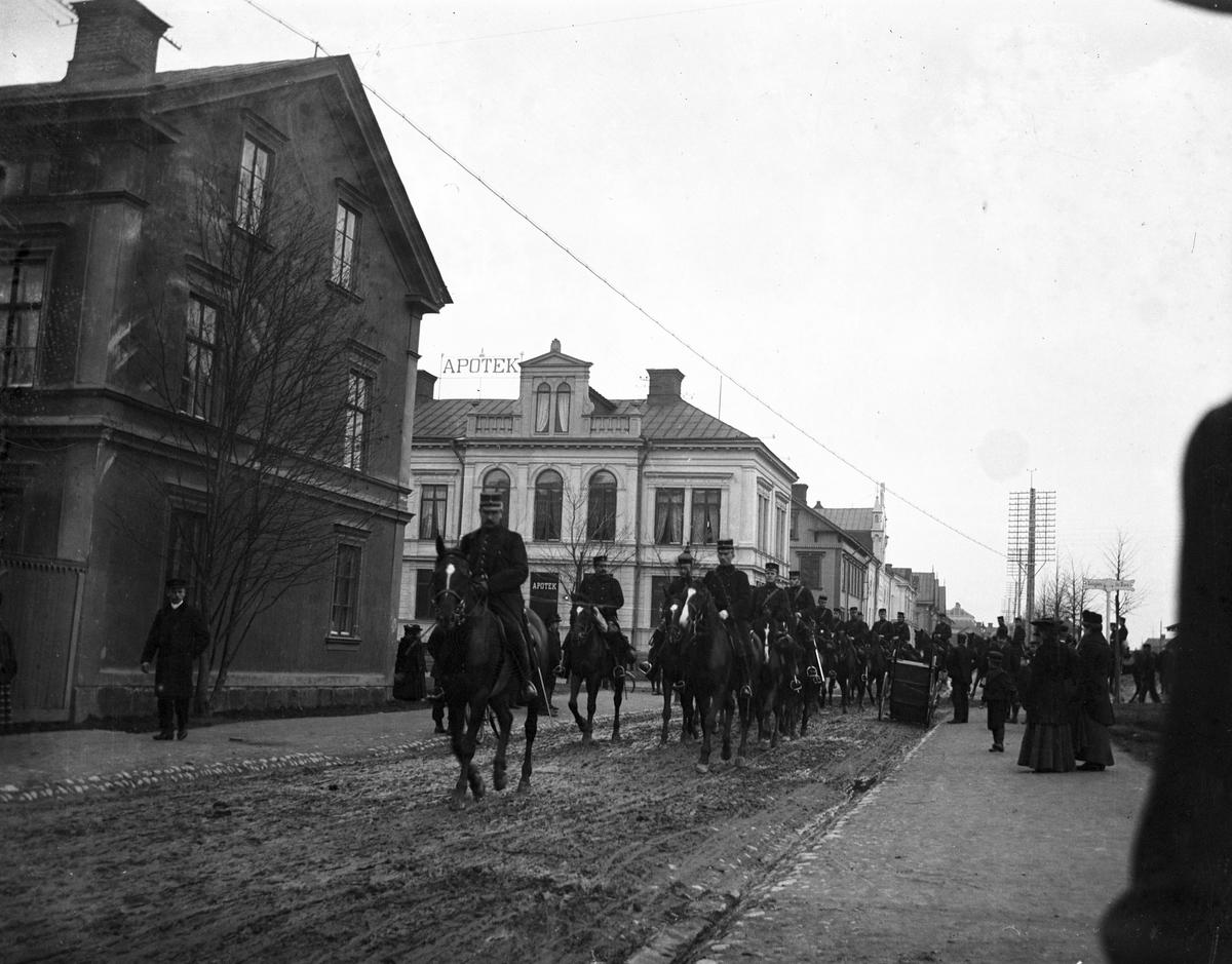 Militärparad vid utställningen 1901. Södra Fältskärsgatan, kvarteret Nya Svan till vänster. Apoteket Kronan, kv Gäddan.