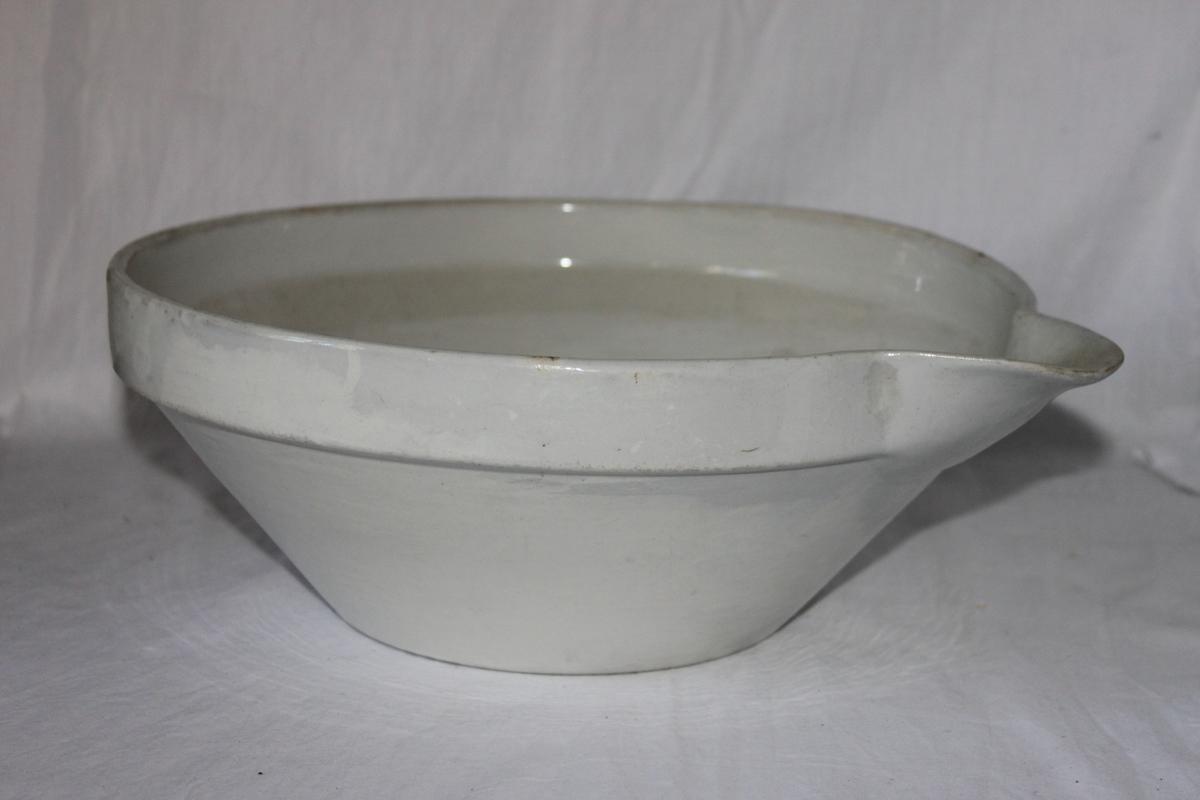 Skål av vitt glaserat flintgods. Från botten, som är 165 mm i diameter, vinklas den raka väggen kraftigt ut för att vid mynningen bli lodrät i 35 mm. Vid mynningen en 90 mm och 50 mm djup snip. För mjölk. Undertill stämplat i godset: IJ, A (understruket) 4.