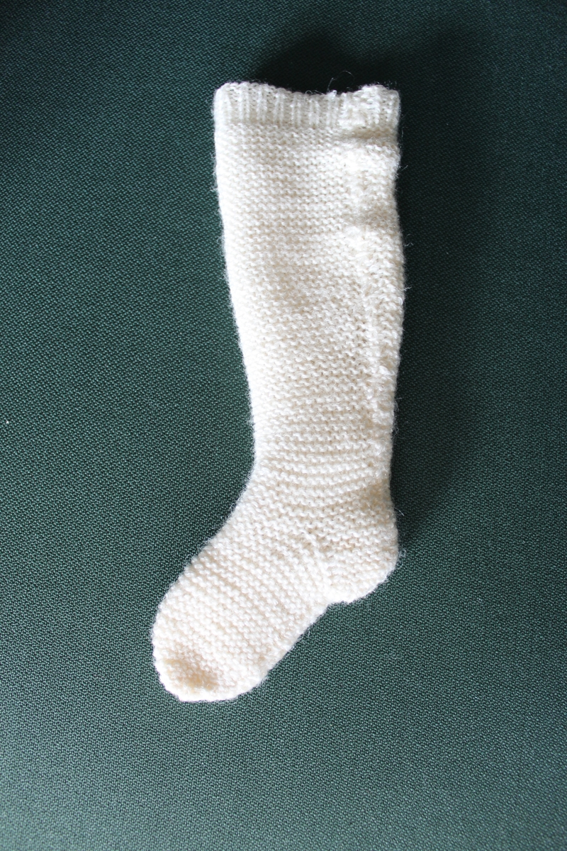 """Dockstrumpa till Shildkrötdockan """"Gunilla"""". Vit lårhög stickad strumpa. Troligtvis tillverkad under sent 1940-tal eller tidigt 1950-tal av sömmerskan Inga Olsson, Anderslundsgatan 12, Västerås."""