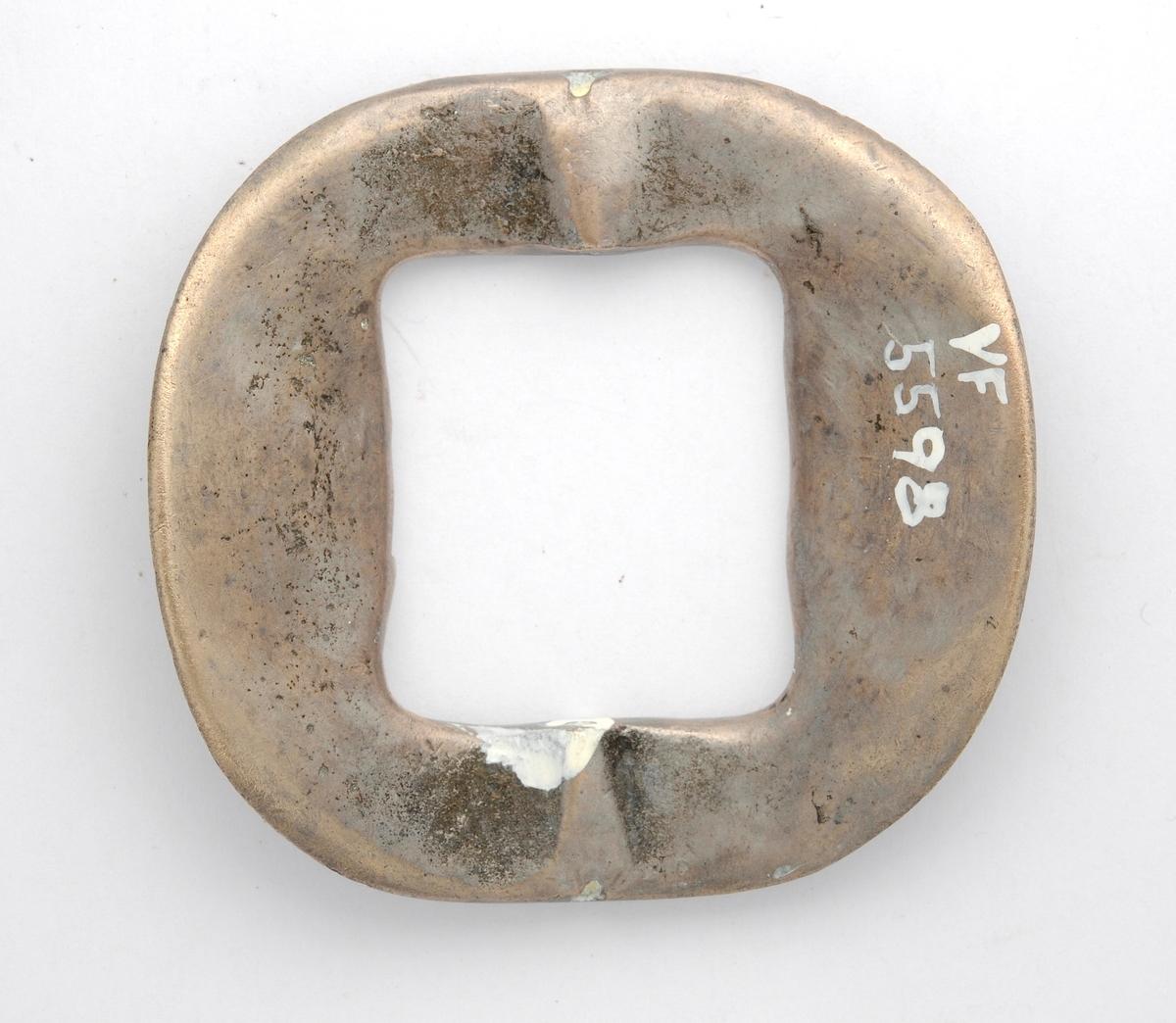 Skospenne i støypt messing belagt med tinn på framsida (?). Hol tvers gjennom spenna til å feste stolpen i. Pedant til VFF 05597.