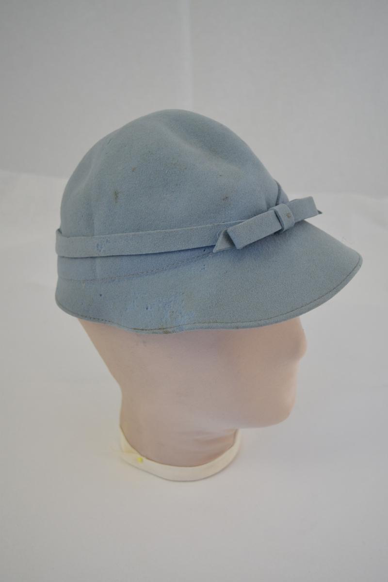 Rund hatt med brem som smalner på hattens bakside. Påsydd bånd med sløyfe. Form: bolleform