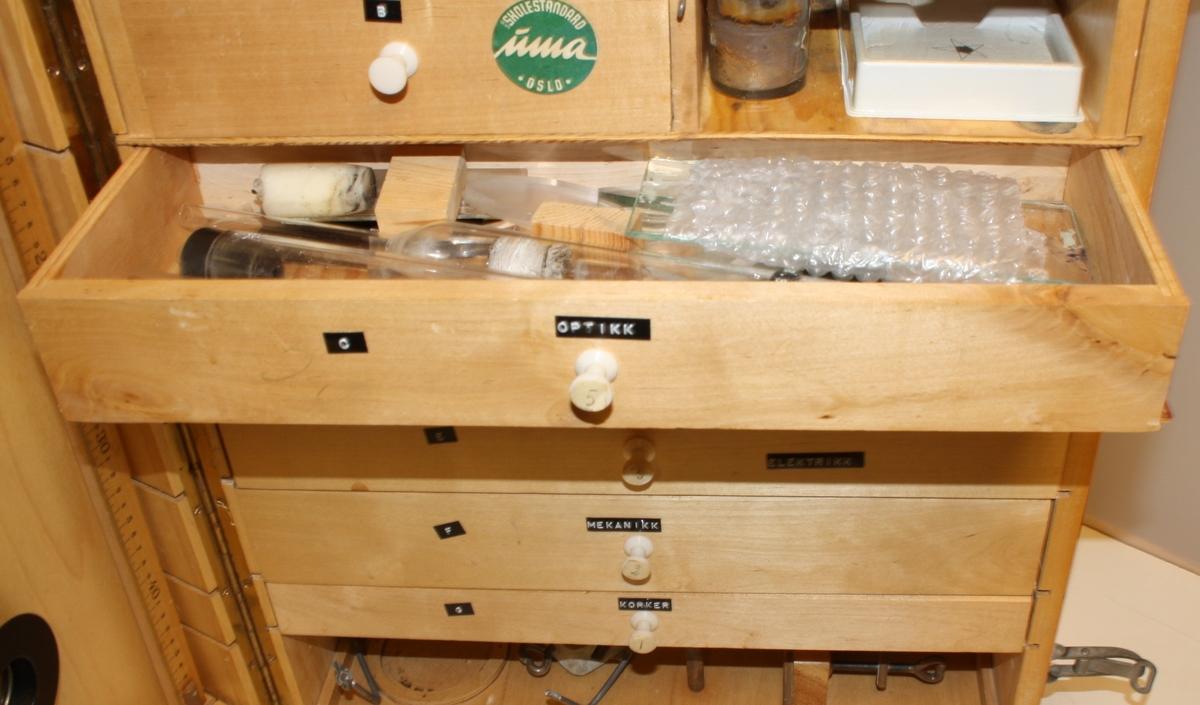 Stor rektangulær trekasse med lok/dør i front og skuffer inni. kassa inneheld lab.utstyr for eksperiment i kjemi, fysikk og elektrisitet.