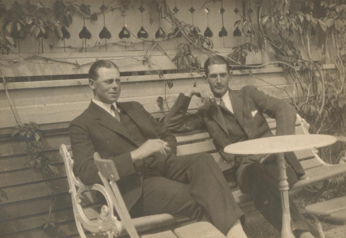 Två finklädda herrar sitter på en uteservering och röker cigarretter.