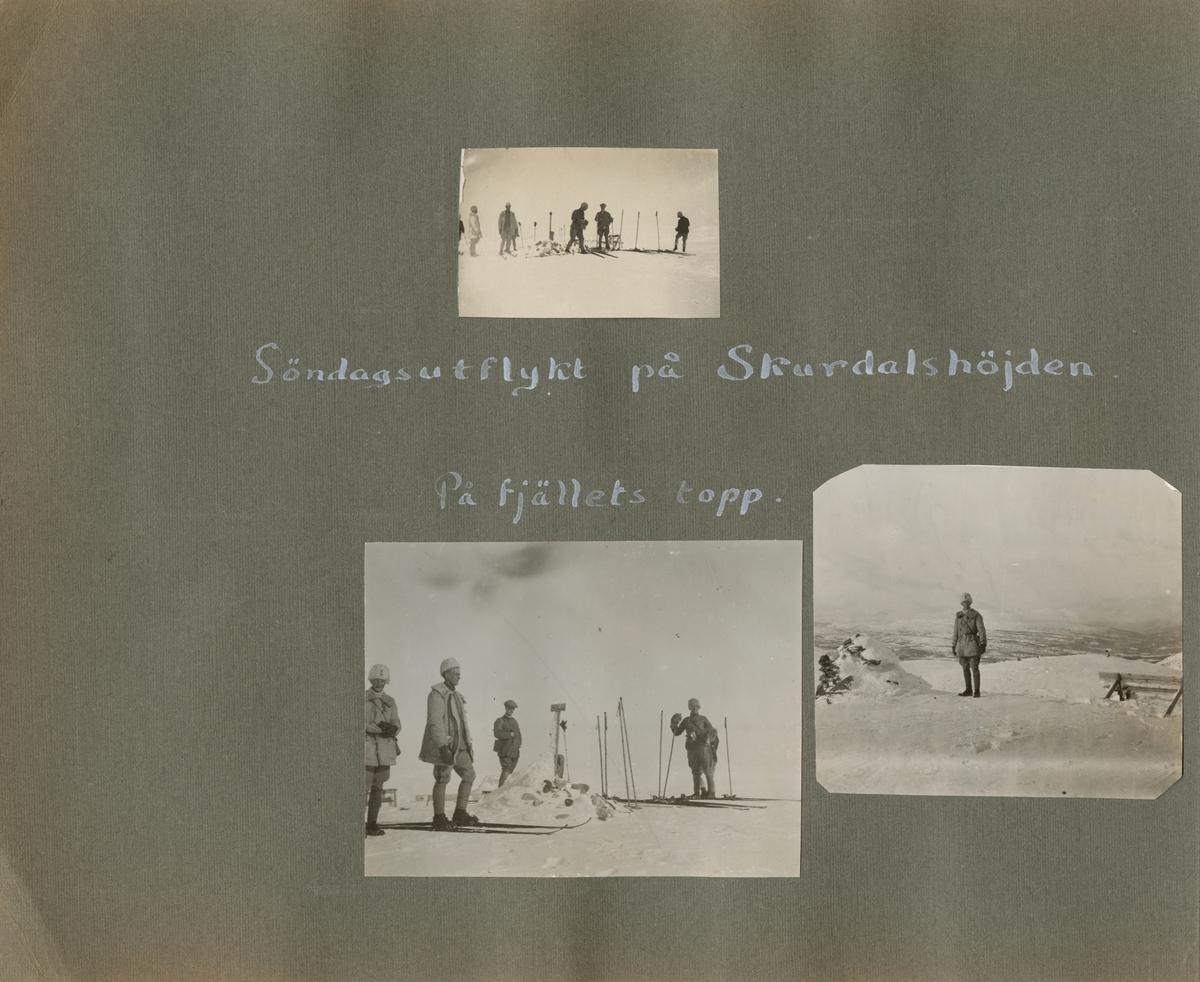En soldat vid ett stenröse och bänk på fjället. Bakom soldaten öppnar sig ett vintrigt fjällandskap med dalgång och fjälltoppar i fjärran.