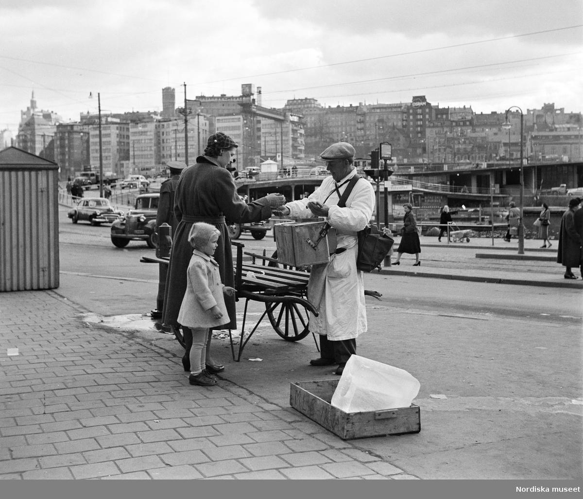 Kvinna och liten flicka köper korv av korvgubbe i Gamla stan.