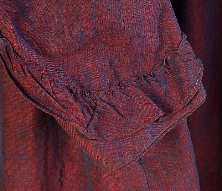 Rödlila klänning med  skiftning av blått, av förr så kallad viktoriavävnad.  Liv: Insvängt, insydda fiskbensfjädrar. Smal, rundad halslinning. Knäppning fram, med 7 st klädda träknappar. I brösthöjd på livets knäppning finns 5 st hyskor och hakar mellan knapparna. 2 st snedsydda insnitt för bättre passform på framstycket. Formsydd rygg i 3 st delar, dekorationssöm med svart tråd. Livet kantat nedtill. Lång tvåsömsärm isydd med passpoal. Påsydd, rynkad volang nedtill på ärmen. Hänghällor fastsydda på baksidan av båda ärmhål. Troligen har liv och kjol varit delade, men är nu hopsydda. Mått: Rygg 40 cm, ärm 57 cm.  Kjol: 7 våder. Rynkparti mitt bak, lagda veck i sidorna, slät fram. Kantad med brickvävda mörkgröna ylleband nedtill. Sparkband av beige- och brunrandigt tuskaftat linnetyg med skarvdel av enfärgat linne.