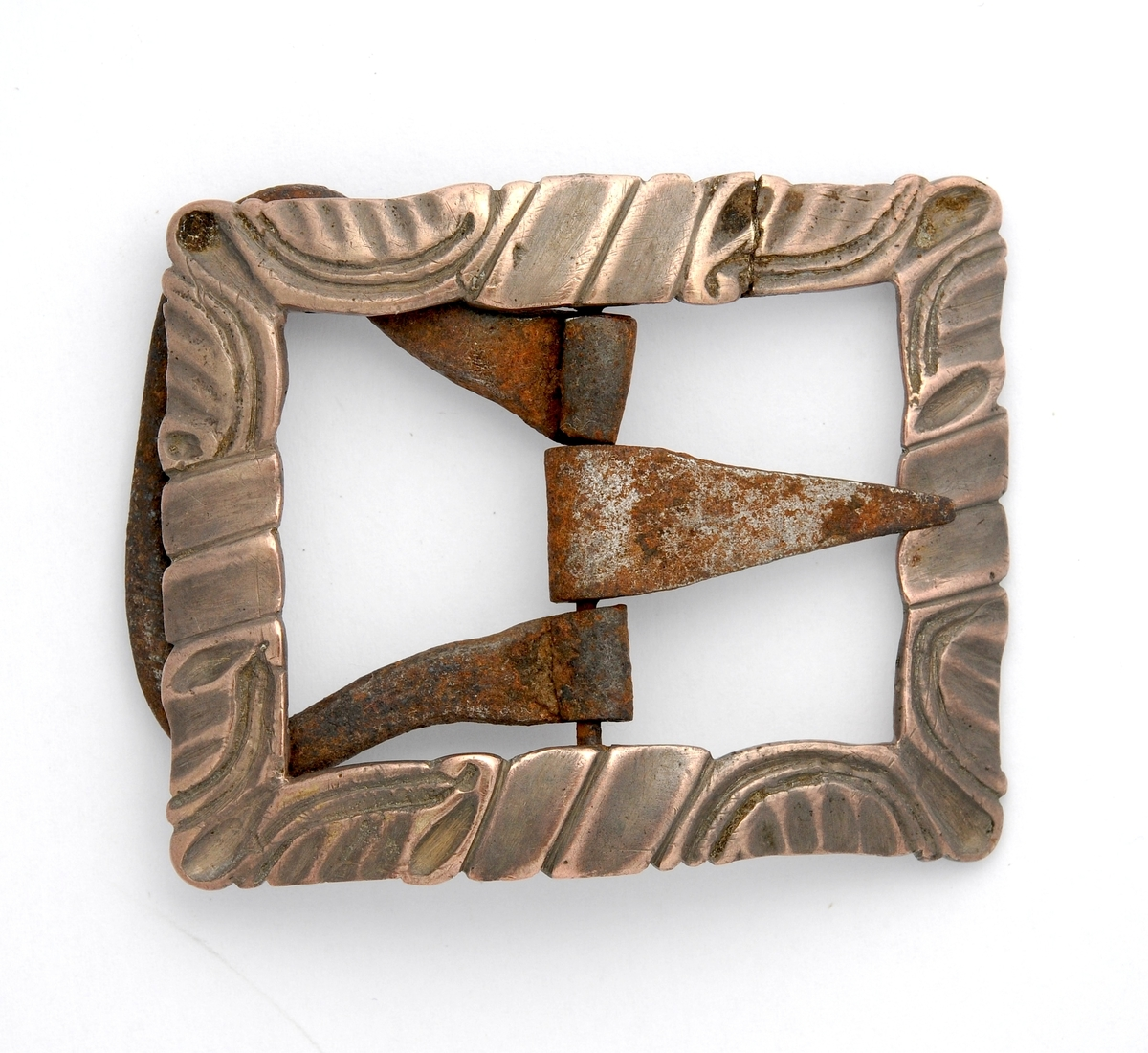 Spenne støypt i messing. Rektangulær form. Stolpe, kalv og tann i smidd jern. Har same mønsteret som VFF 00527.