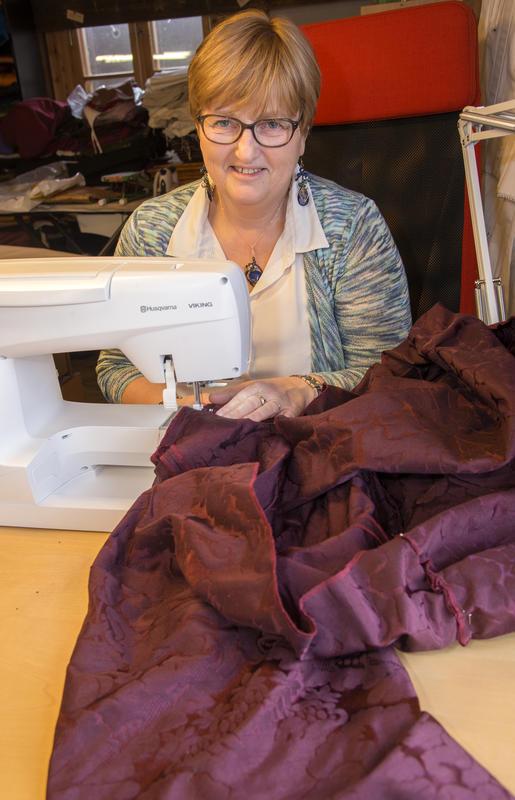 Skredderen sitter bak symaskinen og syr på et plagg i burgunder brokadestoff.