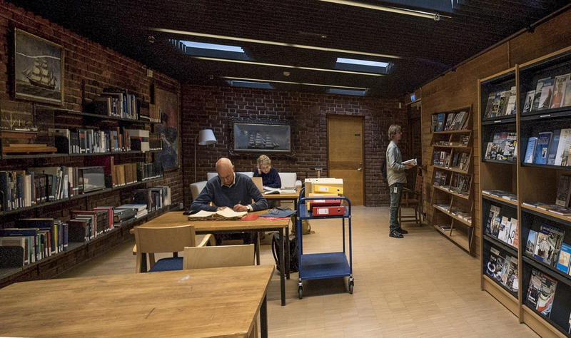 To personer sitter på lesesalen og en person står ved bokhylle på biblioteket. (Foto/Photo)