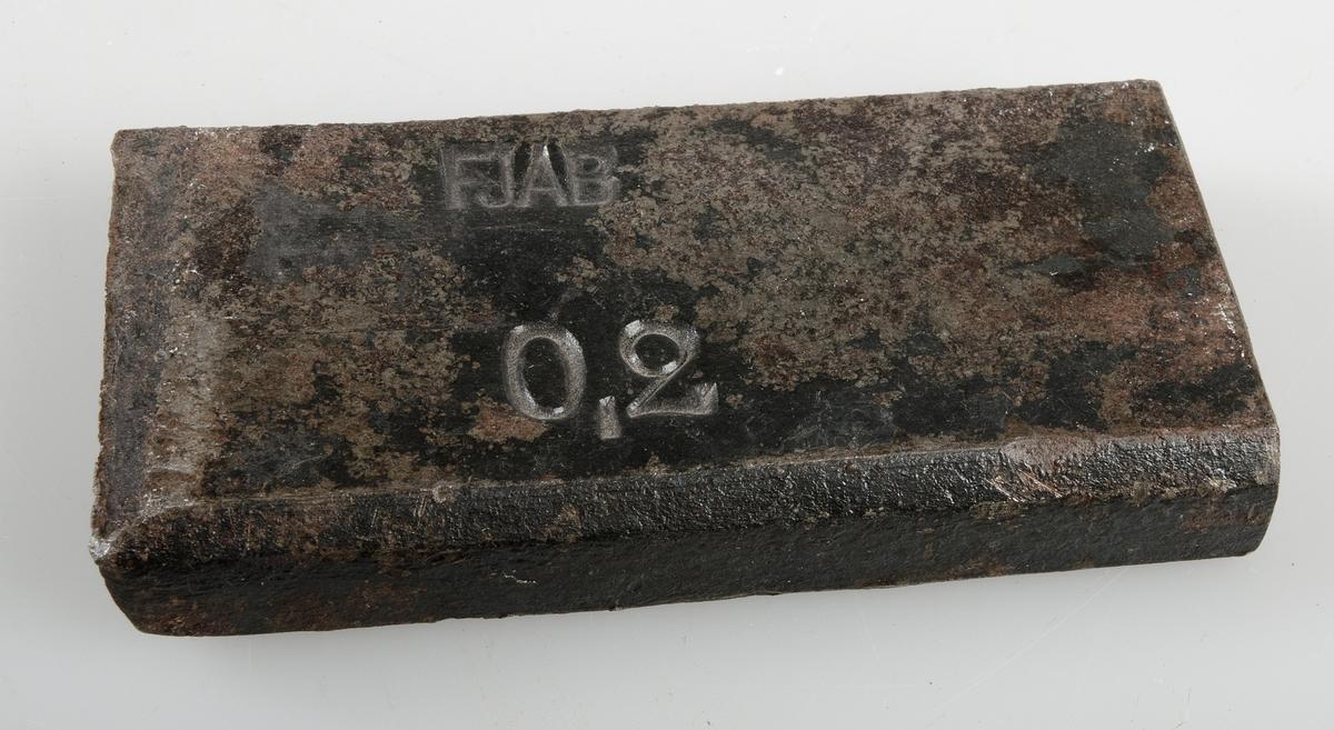 Avhuggen bit av järnstång med stämplar FJAB och 0,2.