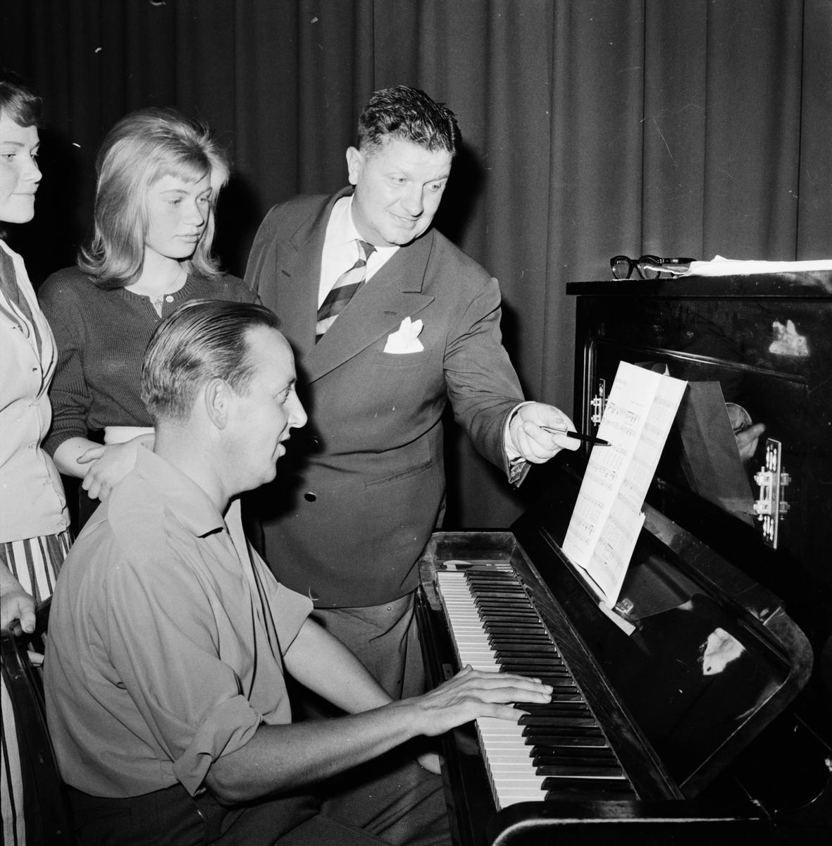 Konferencier med ungdomar vid piano vid repetition inför uppträdande i Slottsbacken.