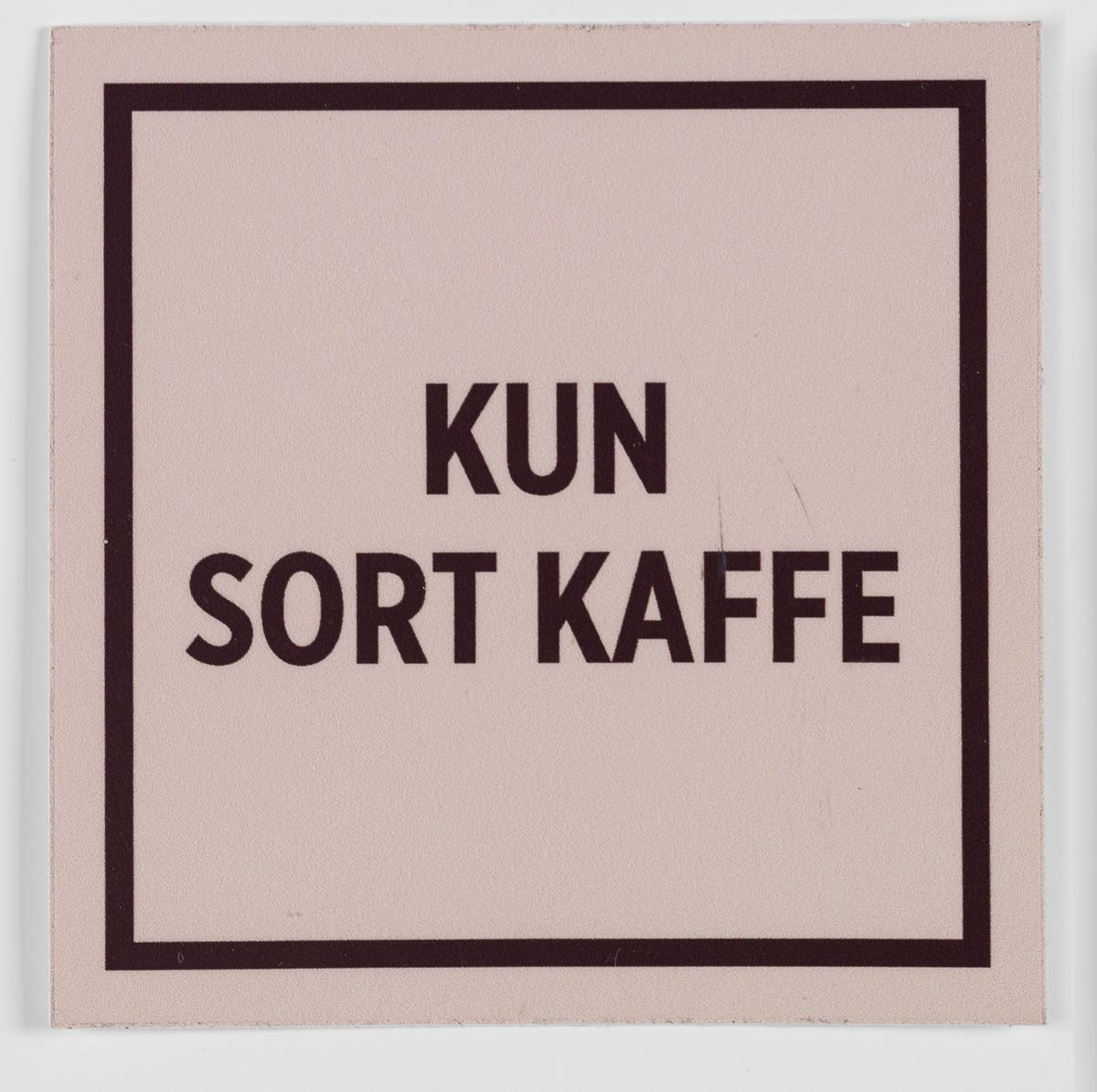 Et kvadratisk klistremerke med stilisert ramme med beige bunnfarge og brun skrift. Kan klistres på en flate i nærheten av kaffeautomaten i butikken.