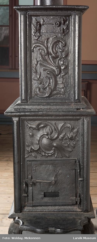 Ovn i  2 etasjer.  Rokokko, jfr. nr 411 i Norsk Jernskulptur b II  1. etasje langside: Mars sitter på en kanon med sverd i høyre hånd. Riflet bunn. 1 etasje kortside: Øverst: Rokokko-ornament, nederst: Grevekrone monogram. FL og 1756  nederst: ovnsdør 2 hengsler ovalt askebrett med profilert kant. 2.etasje langside: Fyldig rokokko-ornament. med blomster. Uregelemessig portalåpning.  2. etasje kortside: Rokokko-ornament,  Ovnen har sungne ben m/dyreføtter