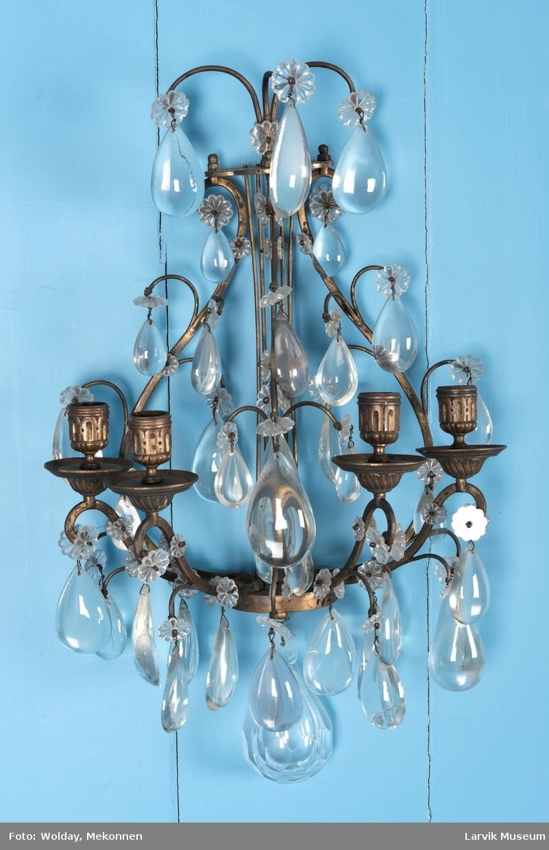 Lyreformet med 4 lyseholdere, dråpeform. Prismer festet ved blomster i krystall