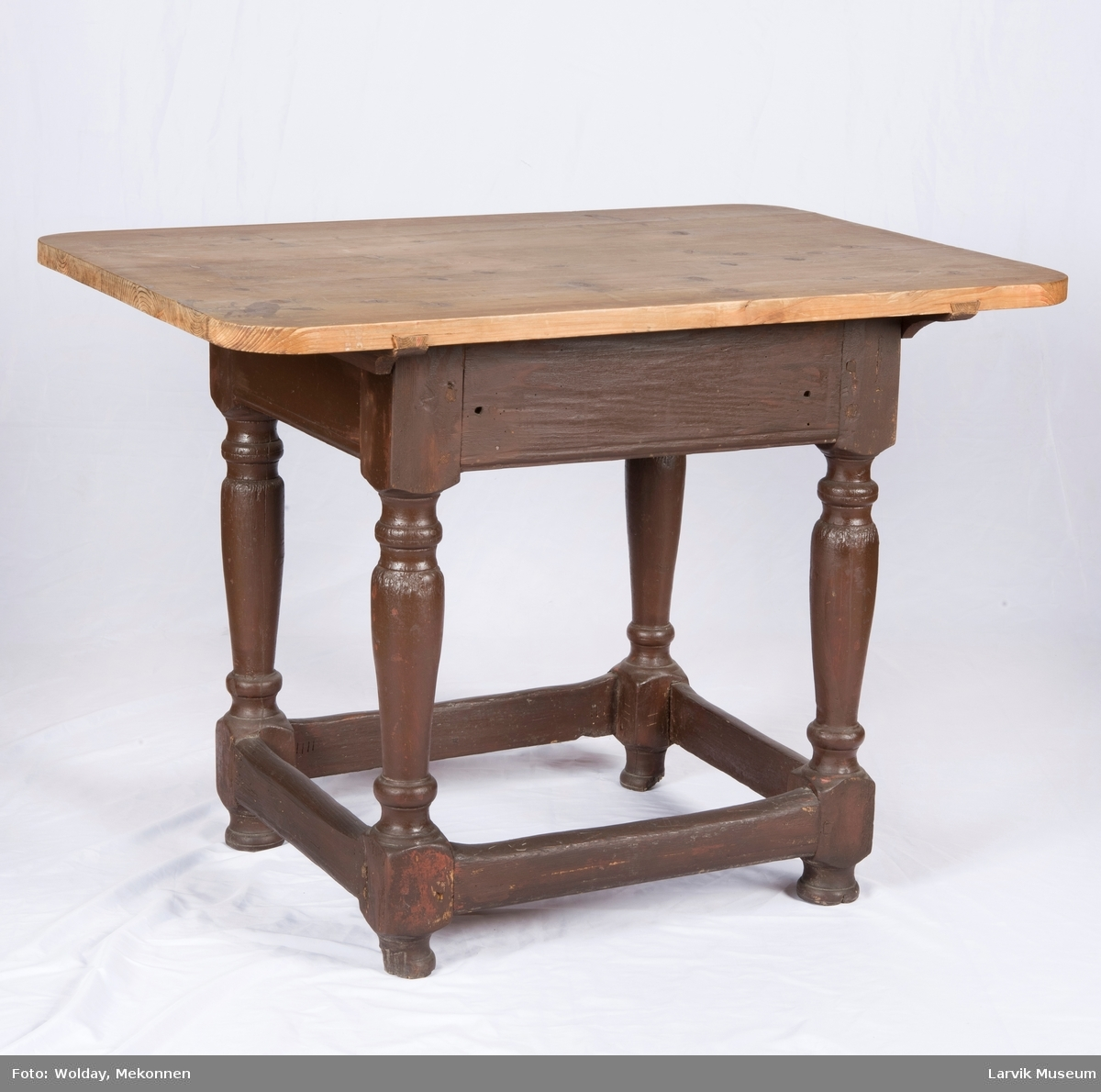 Rektangulær bordplate med avrundede hjørner, sammen- satt av 4 deler, festet med trenagler til sarg. Dreide ben, forbundet med rett sprosseverk. En skuff på langsiden.