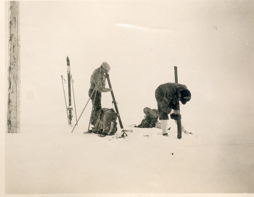 To menn smører ski. Telegrafstolpe. Snø.