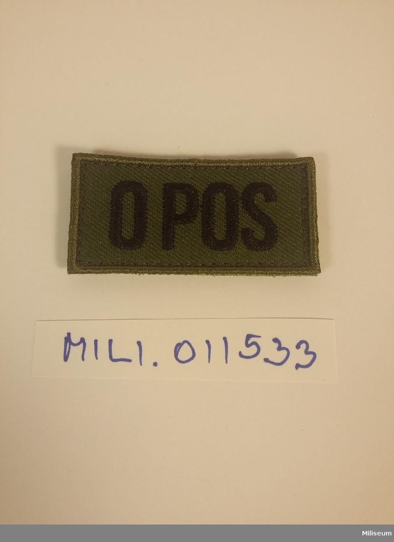 """Tilläggstecken med texten """"O POS"""". Med kardborreväv på baksidan."""