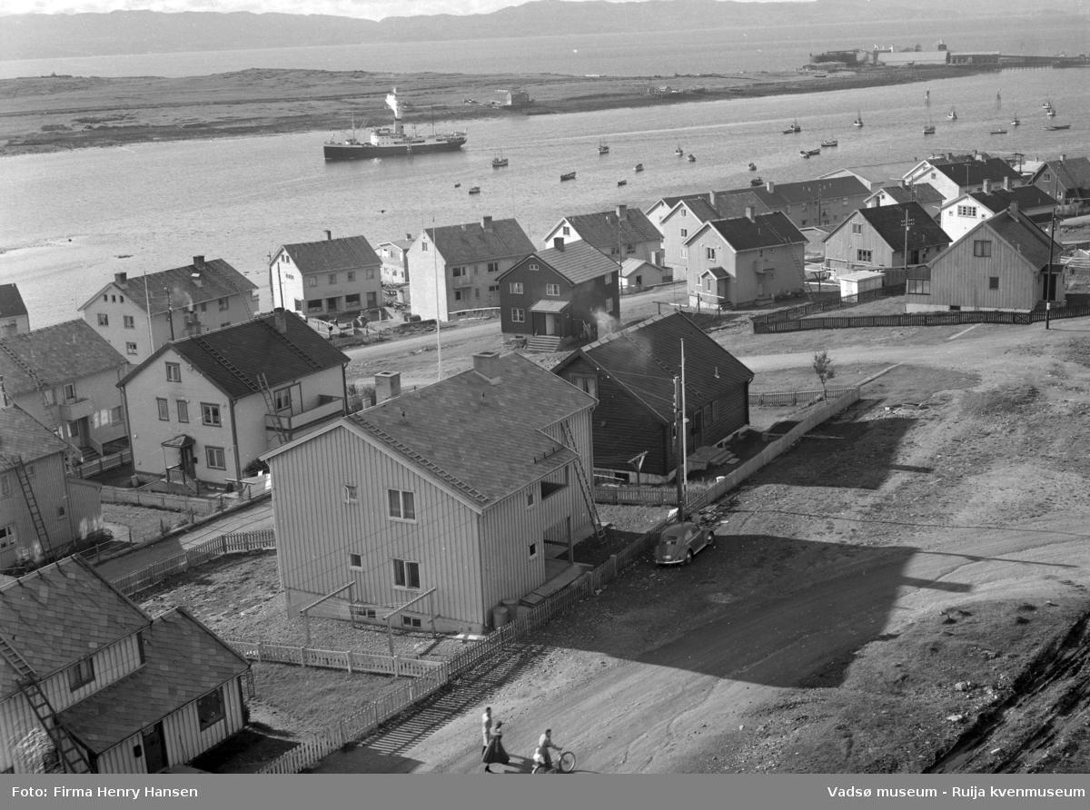 Vadsø 1957. Bildet er tatt fra kirken som sto ferdig i 1958. Bildet er tatt mot sydøst og viser boliger langs Damsveien, Nyborgveien og opp langs Tollbugata. Vi ser også litt av havna og Vadsøya. Hurtigruta er på vei inn i havna og vi ser fiskebåter og småbåter ankret opp i havna. På øya ser vi bygninger og kaier, fiskebruk. I høyre billedkant, mot vest ser vi Vadsø Sildoljefabrikk.