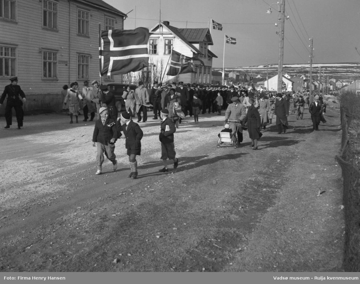 Vadsø 17 mai 1951. Bildet er tatt mot øst. 17 maitoget, muligens folketoget, marsjerer i Ytrebyen. I høyre bakkant av bildet ser vi Melkevarden, litt snedekket,  Midt i blidet ser vi 17. maitoget, folketoget. Først i toget går flaggbærer og antagelig 17.maikomiteen. Rett bak kommer et stort antall marinegaster marsjerende. Langs toget tre gutter i toppluer. Videre ser vi kvinner og menn gående og noen med sykkel, barnevogn.
