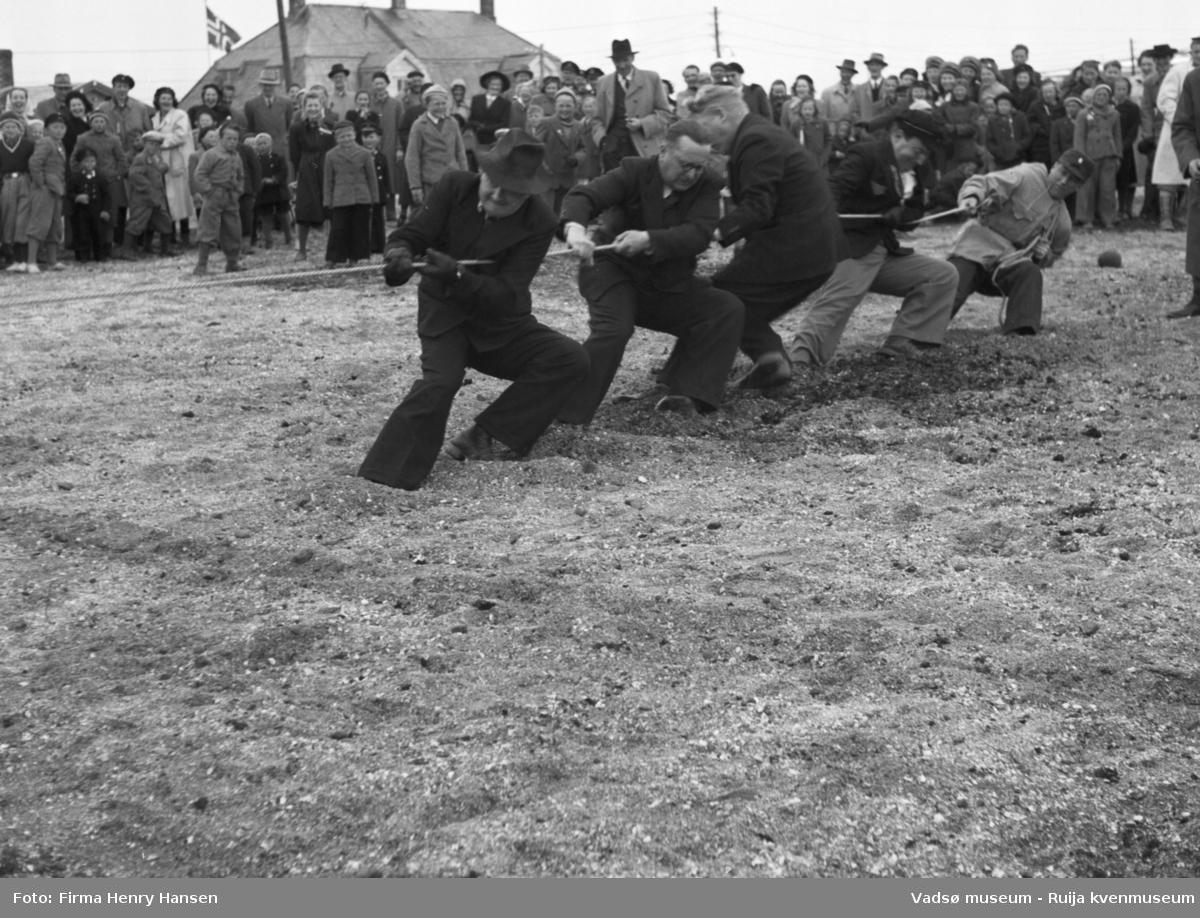 Vadsø 17 mai 1951. Tautrekkingskonkurranse. I enden av tauet ser vi fem menn, en med hatt, som trekker i tauet. En stor menneskemengde, barn og voksne, står og bivåner det hele.  I menneskemengden ser vi barn og voksne, kvinner og menn.