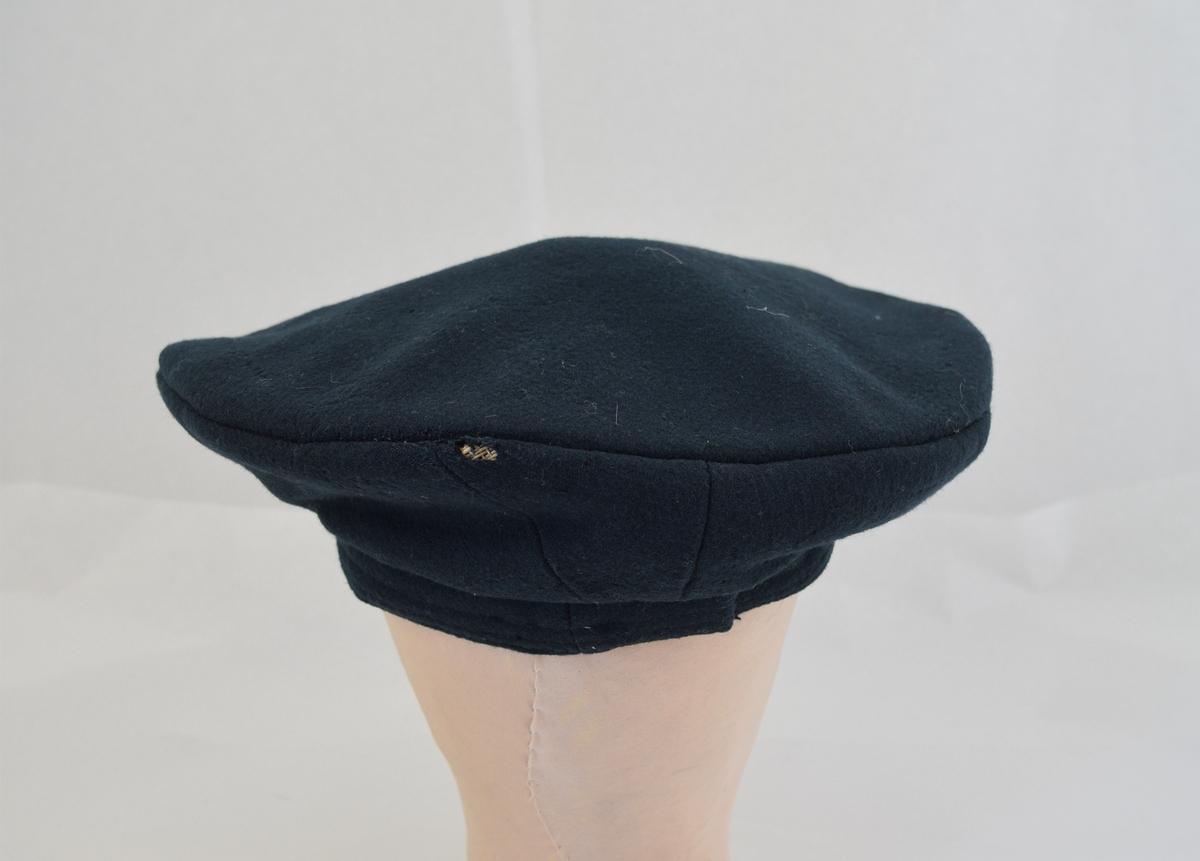 Form: Rund flat lue m/liten kant rundt åpningen. For av tynt tekstil.