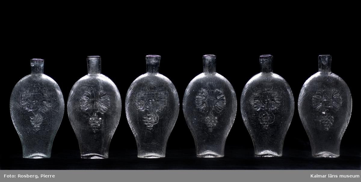 KLM 23287. Brännvinsflaskor av pressglas, 6 stycken. Av typen fickplunta. Höjden varierar något mellan 18,5 cm till 19,2 cm.