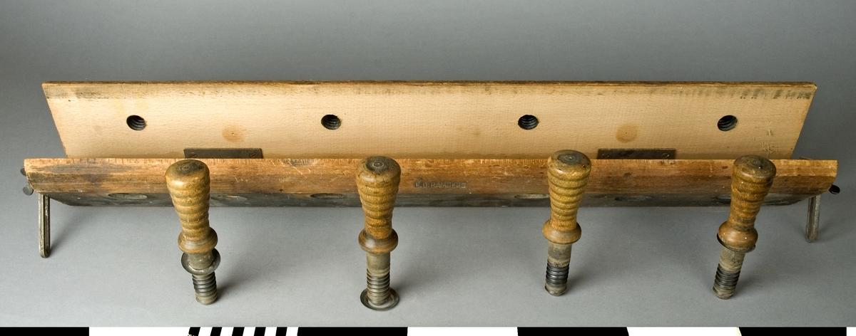 Filklov av bok. Filkloven består av två stycken 120 mm breda trästycken som på den ena långsidan är förbundna med varandra med två gångjärn. På den andra långsidan är trästyckerna avrundade så att de bildar en cirkelformad avslutning då de trycks samman. På denna sida av filkloven spännes det stycke fast som skall filas. Fastspänningen sker med hjälp av fyra träspindlar som jämnt fördelade går genom båda trästyckena. Träspindlarnas handtag är svarvade med dekorränder. På samma sida som träspindlarna finns två hål med gängor. Den långa filkloven användes bland annat för filning av bandsågblad. Filkloven fastspännes mellan hyvelbänkens hakar. Kloven är stämplad EG RAMBERG.  Funktion: Fasthållning av sågblad vid filning och skränkning