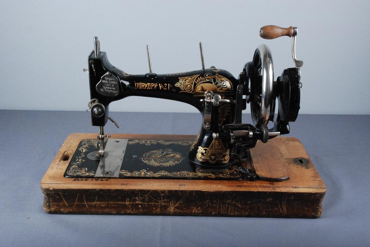 Symaskin på rektangnelformet sokkel. Håndsveiv som felles ut ved bruk. Maskinen står på en rektangulær sokkel som har et rom med svingbart lokk. Rektangelformet buet deksel.