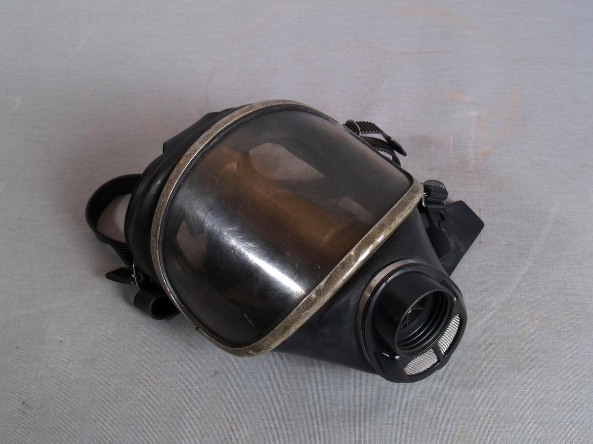Gassmaske i gummi, med plastvindu i ramme av metall. Ventil i plast med metallgitter. Gjenget tilslutning for filter. Regulerbare gummi  remmer for feste rundt hodet