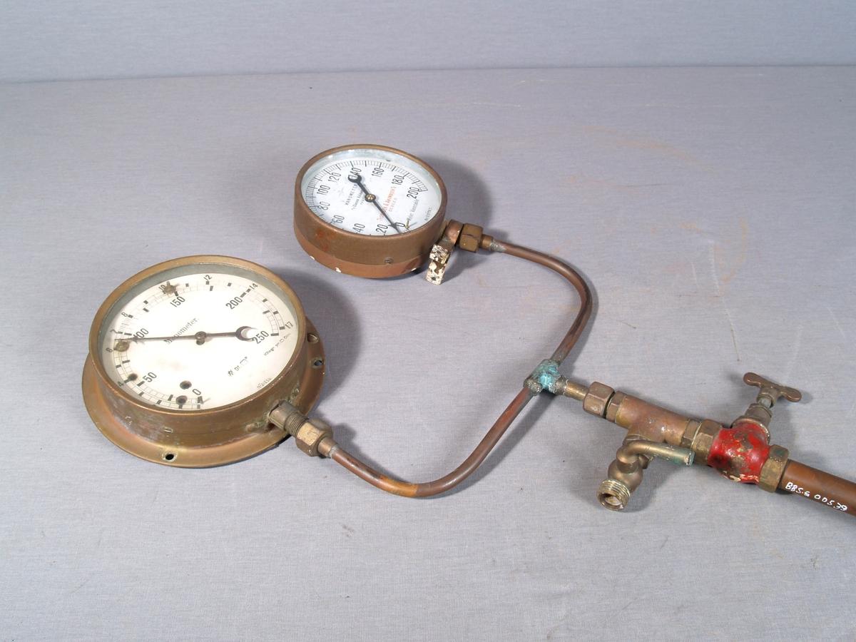 Trykkmåler for vannverket. To runde måleinstrumenter montert ved siden av hverandre på et kobberrør. To kranhendler under festepunktet for manometrene. Røret har en bøy omlag midt på.