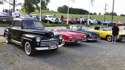Mange biler oppstilt som utstilling på en parkeringsplass.  Mennesker som går og ser på bilene.. Foto/Photo