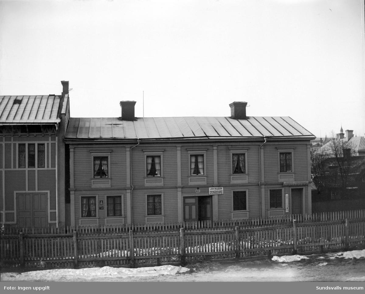 """Bostadshus efter Norrmalmsgatan 7-9. Skyltar på fasaden: """"Joh. Nilsson SKRÄDDARE"""" samt Ernst Westman URMAKARE""""."""